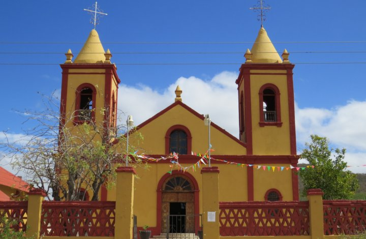 yellow and red church in old mining town in baja