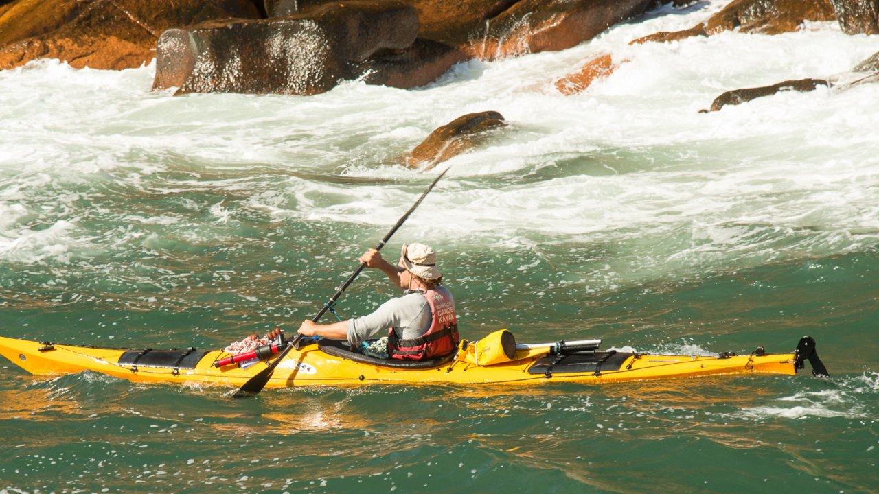 sea kayak in foamy water in front of rocks