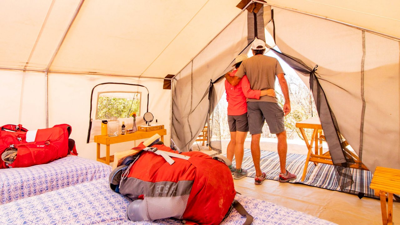 people in baja glamping tent