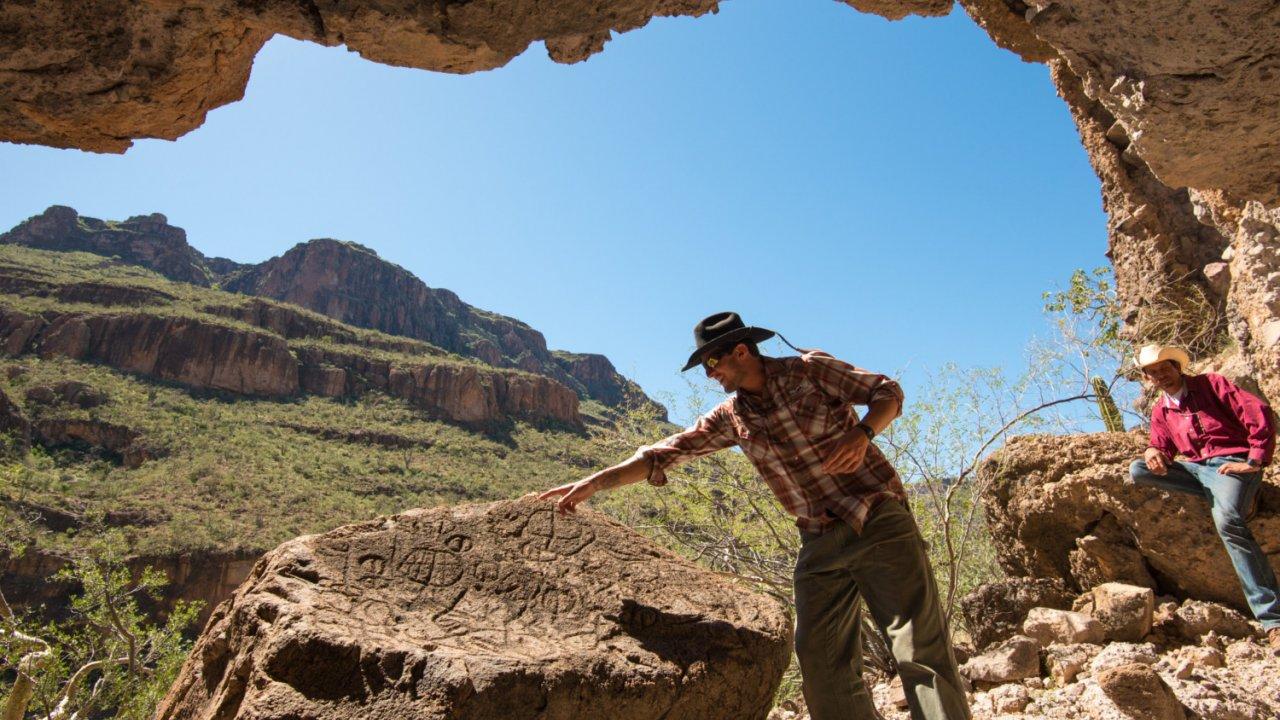 man looking at rock art in baja