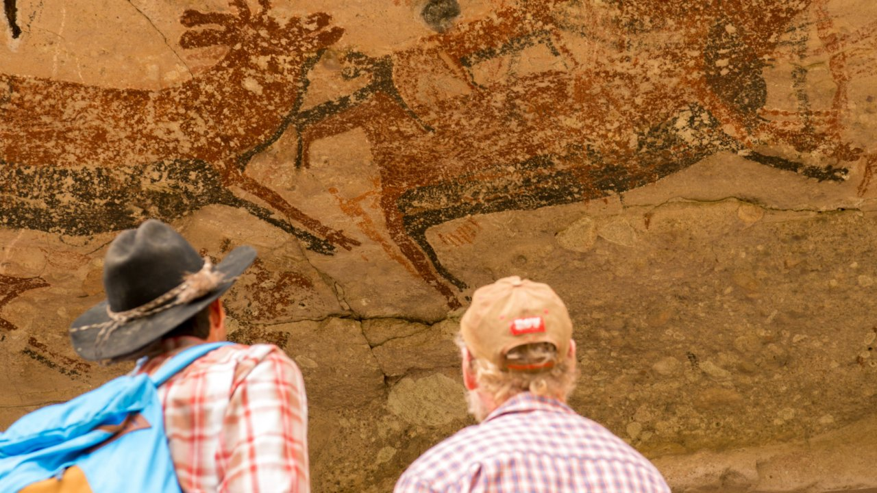 men looking at prehistoric rock art in Baja California Sur