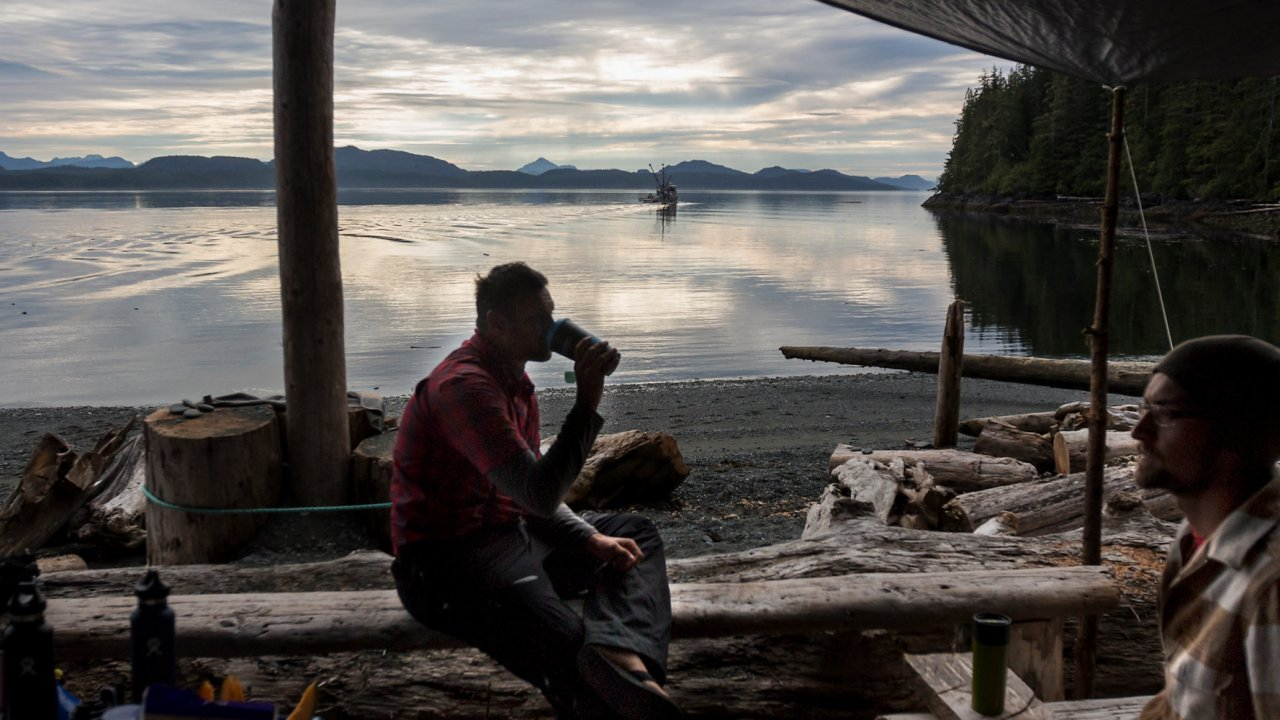 man sitting on log along vancouver island shore