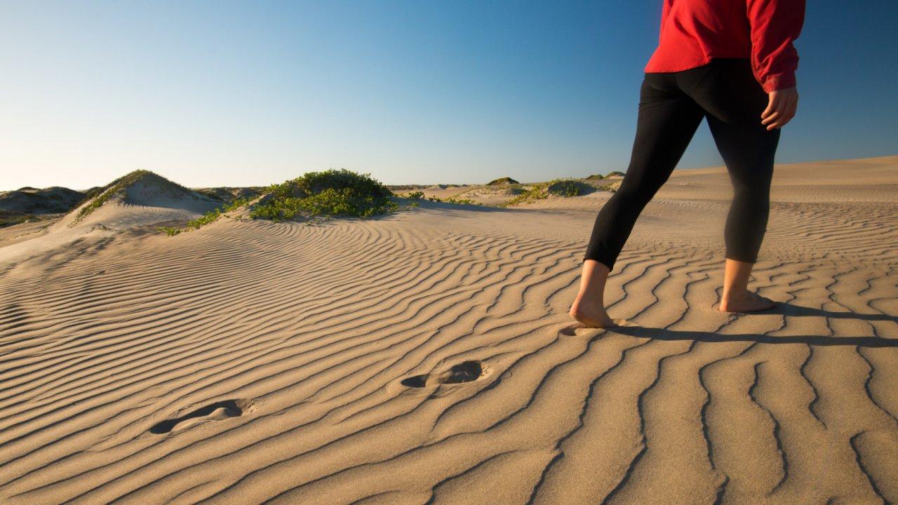 woman walking across sand dune