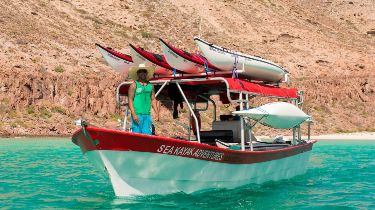 panga with sea kayaks on it