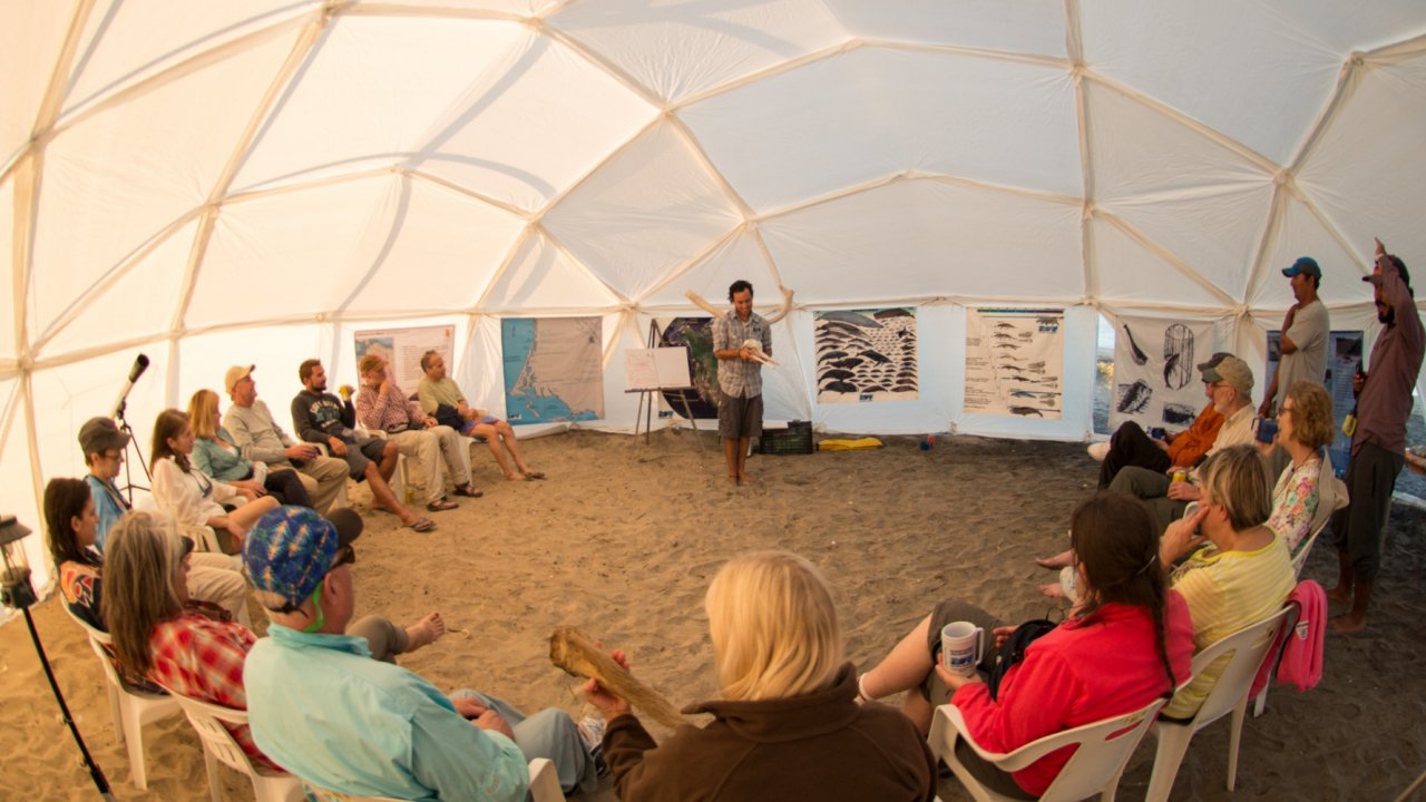 group of travelers listening to whale presentation in dome tent
