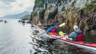 sea kayakers paddling along shore of vancouver island