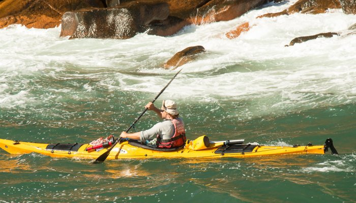 sea kayak in foamy water in front of rocks