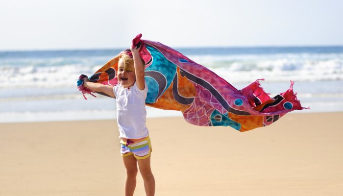 child with sarong on beach